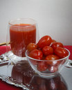 Tomato and juce on silver Royalty Free Stock Images