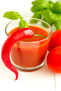 Tomato juice chili pepper and basil leaf on white wooden backgro Stock Photos