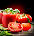 Tomato juice and fresh tomatoes with basil on a wooden table Royalty Free Stock Photos