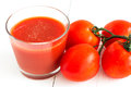 Tomato juice in glass and tomatoes Stock Images