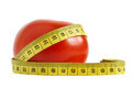Tomato and measuring tape over white background the concept of dieting health Stock Photo