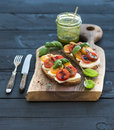 Tomato, mozzarella and basil sandwiches on dark wooden chopping board, pesto jar, dinnerware over black background Royalty Free Stock Photo