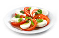 Tomato and mozzarella salad on white plate Royalty Free Stock Photos