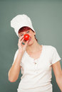 Tomato nose young female cook holding on her Stock Photography