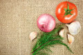 Tomato onion and garlic vegetables on sacking background texture Stock Photos