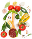Tomato pasta sauce in a wooden spoon and fresh ingredients on a white from top view Stock Photos