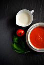 Tomato soup with basil overhead shot of fresh single cream and herbs selective lighting copy space Stock Image