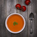 Tomato soup vintage a bowl of with a tarnished silver spoon and fresh vine tomatoes against a rustic wood tabletop style with Stock Image
