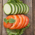 Tomato and  zuchini slices on wood table. Royalty Free Stock Photo