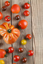Tomatoe border made from yellow red and black tomatoes on wooden background Stock Images