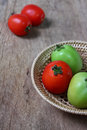 Tomatoes in bamboo basket on wooden background textured Stock Images