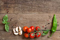 Tomatoes, basil, mint, garlic and pepper on dark wood Royalty Free Stock Photo