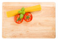 Tomatoes basil and uncooked spaghetti on a cutting board viewed from above isolated on white Stock Photo