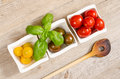 Tomatoes basil and wooden spoon in bowls Royalty Free Stock Photography