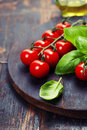 Tomatoes with basil on wooden table background food composition Royalty Free Stock Images