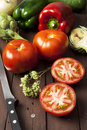 Tomatoes bell peppers and artichoke with knife on a brown wooden table vertical composition Royalty Free Stock Photography