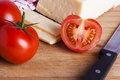 Tomatoes and cheese with knife on chopping board Royalty Free Stock Photo