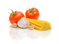Tomatoes, garlic and pasta on a white background Stock Photography