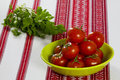 Tomatoes in a green bowl and parsley on the table ripe Royalty Free Stock Photo