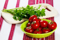 Tomatoes in a green bowl and parsley on the table ripe on cutting board Royalty Free Stock Image