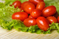 Tomatoes and lettuce vegetarian tomato on bamboo tray are photographed close up Stock Photos