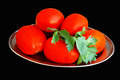 Tomatoes on a metal plate black background Royalty Free Stock Image