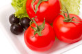 Tomatoes and olives on the lettuce leaf Royalty Free Stock Photography