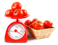 Tomatoes on scales and in a basket. Royalty Free Stock Photo