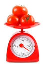 Tomatoes on scales. On white background. Royalty Free Stock Photo