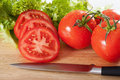 Tomatoes sliced horizontal close up of fresh situated on cutting board Royalty Free Stock Photos