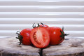 Tomatoes slicing on a wooden chopping board Royalty Free Stock Photo