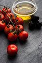 Tomatoes twig with olives and olive oil on the dark stone table Royalty Free Stock Photo