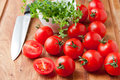 Tomatoes on wooden cutting board thyme herb and knife selective focus shallow dof Stock Photography