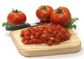 Tomatoes on wooden cutting board whole and sliced and knife Stock Images