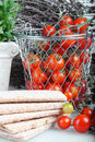 Tomatos cherry type in a wired metal basket with herb background and cracker detail Stock Photos