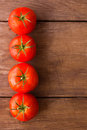Tomatos on rustic wood background Royalty Free Stock Photo
