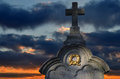 Tombstone cross with golden wreath and dramatic sunsdown Stock Photos