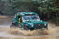 Tomcat off roading bagshot uk march an unnamed driver of a road comp safari land rover takes a wet section of the track at speed Royalty Free Stock Photos
