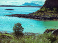 Toned image lonely man floating on the Norwegian sea through the Lofoten Islands against the backdrop of mountains and sky Royalty Free Stock Photo
