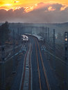Toned image of the railway with sleepers and rail bridge on a background of multicolored sunset clouds in sky Stock Photography