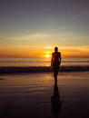 Toned image of a silhouette of an adult woman walking on the beach at sunset Royalty Free Stock Photo