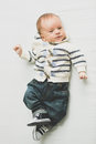 Toned photo of baby boy in jeans and sweater lying on bed Royalty Free Stock Photo