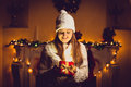 Toned portrait of cute woman in sweater and hat holding glowing gift box at decorated christmas room Royalty Free Stock Photo