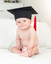 Toned portrait of smiling baby boy in graduation hat looking in Royalty Free Stock Photo