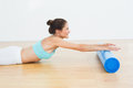 Toned woman doing the stretching exercise in fitness studio side view of a young Stock Photo