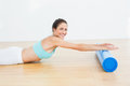 Toned woman doing the stretching exercise in fitness studio side view of a young Stock Photos