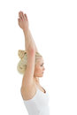 Toned woman with joined hands over head side view of a young against white background Royalty Free Stock Photo