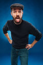 The tongue hanging out man in cap on blue background Royalty Free Stock Photography