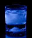 Tonic water and lemon in black light highball tumbler glows blue ultraviolet Royalty Free Stock Photos