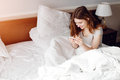 TONING smiling young woman browsing web with phone on bed Royalty Free Stock Photo